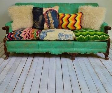 Потертый зеленый диван с пестрыми подушками