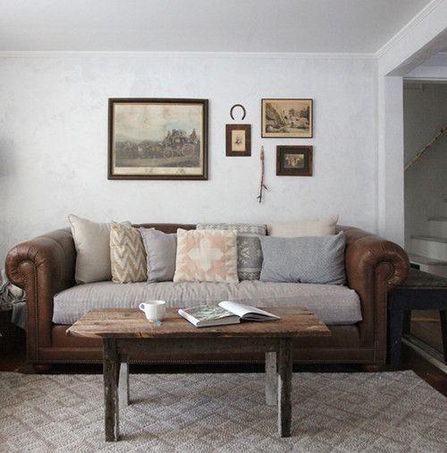Кожаный диван с тканевыми подушками в интерьере гостиной