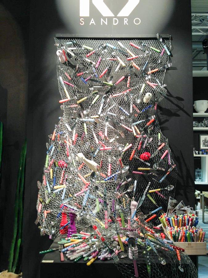 Любопытный декор выставочного стенда из разноцветных ложек и вилок
